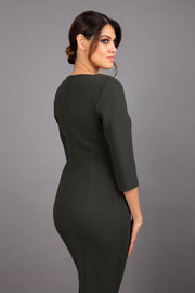 Brunette model wearing Diva Catwalk Lovell Pencil Dress in Obsidian Green with lowered sweetheart neckline and three quarter sleeve with gathering at the bust back