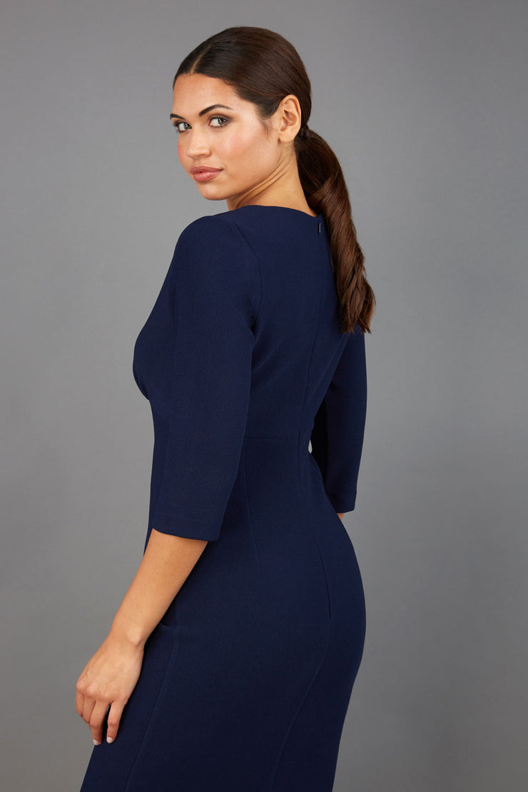 Brunette model wearing Diva Catwalk Lovell Pencil Dress in Navy  with lowered sweetheart neckline and three quarter sleeve with gathering at the bust back