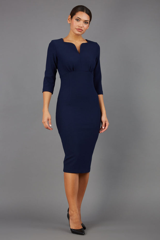 Brunette model wearing Diva Catwalk Lovell Pencil Dress in Navy  with lowered sweetheart neckline and three quarter sleeve with gathering at the bust front