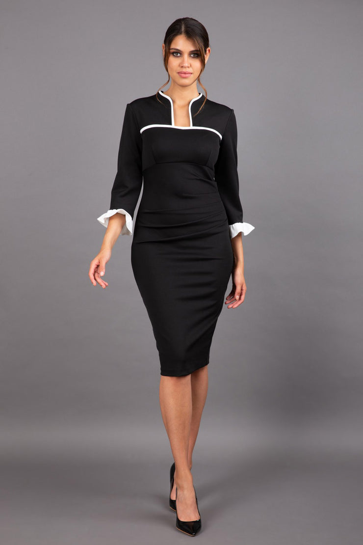 brunette model wearing Diva catwalk masie dress in black and ivory with Elizabethan Collar and contrasted high neckline