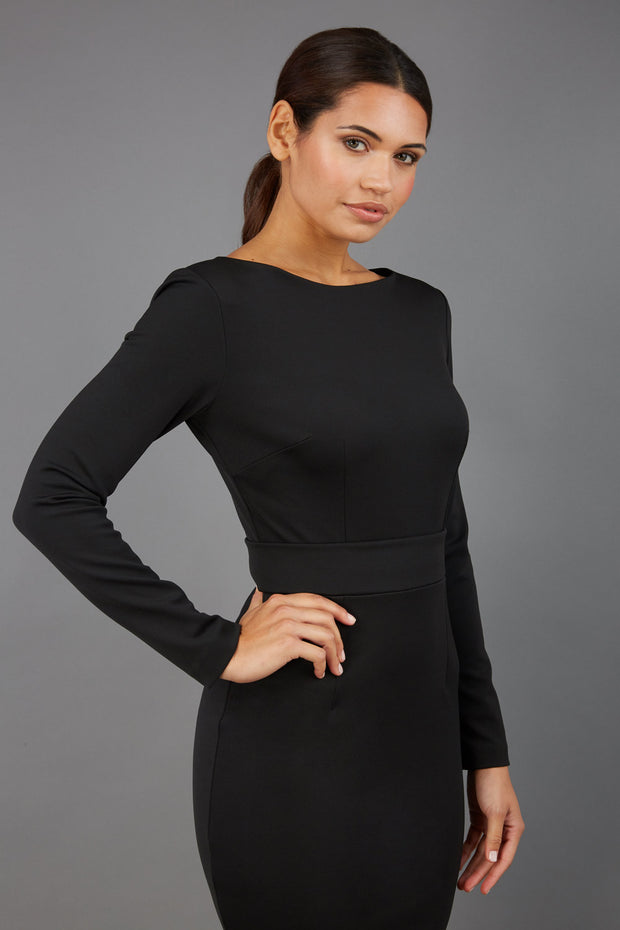 brunette model wearing diva catwalk tessa little black dress with boat neckline and long sleeves with a band front