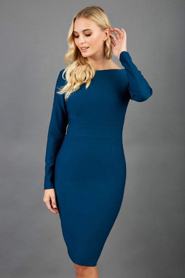 blonde model wearing diva catwalk tessa little glorious teal dress with boat neckline and long sleeves with a band front