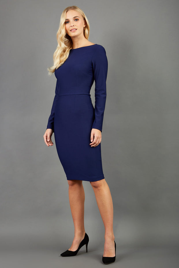 brunette model wearing diva catwalk tessa navy dress with boat neckline and long sleeves with a band front