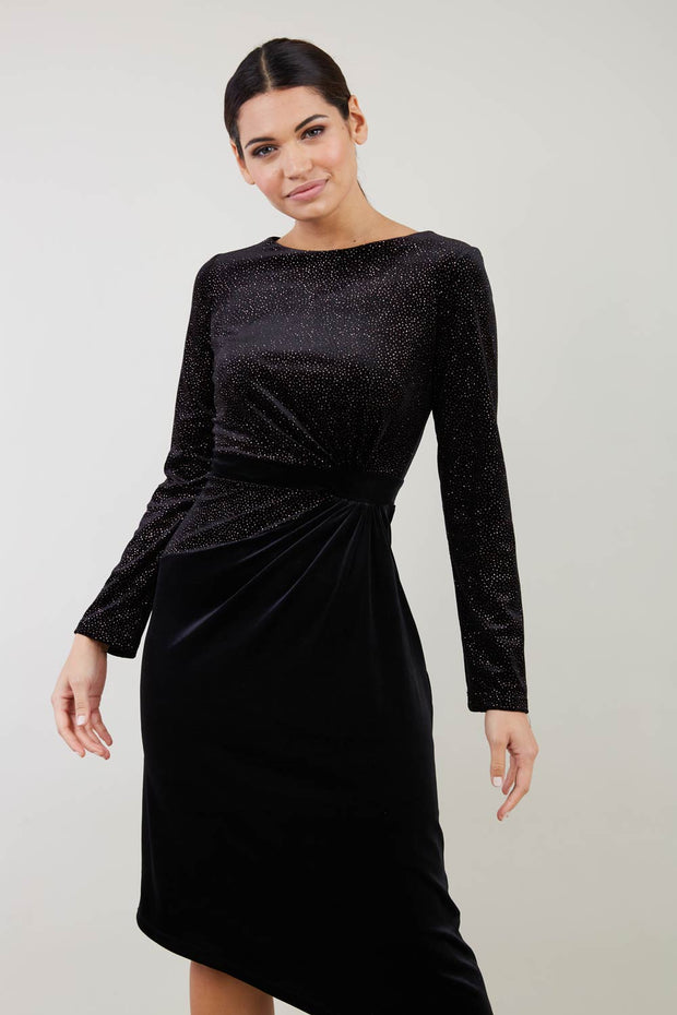 Brunette Model wearing assymetric glitter and black velvet long sleeve dress front image