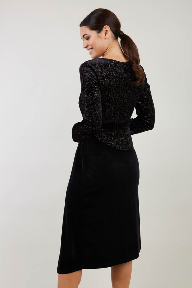 Brunette Model wearing assymetric glitter and black velvet long sleeve dress back image