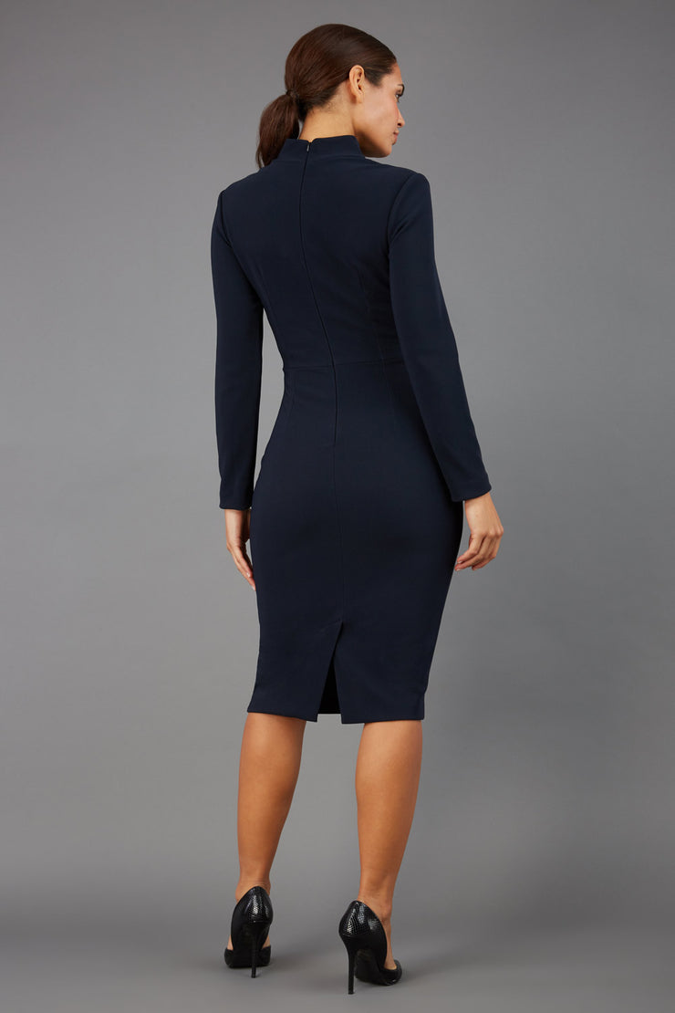 brunette model wearing diva catwalk sasha pencil-skirt dress with long sleeves and high neck in colour dark blue back