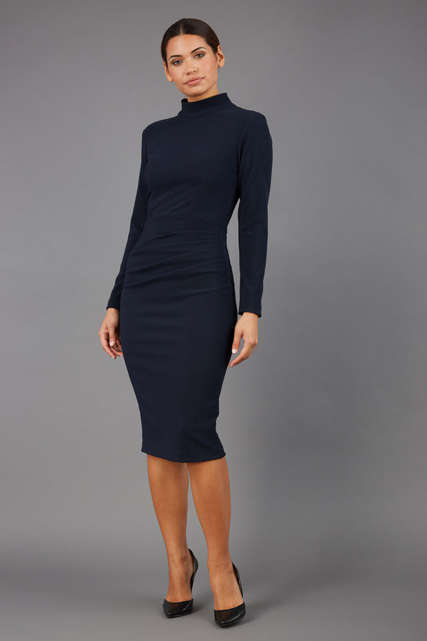brunette model wearing diva catwalk sasha pencil-skirt dress with long sleeves and high neckline in colour dark blue front
