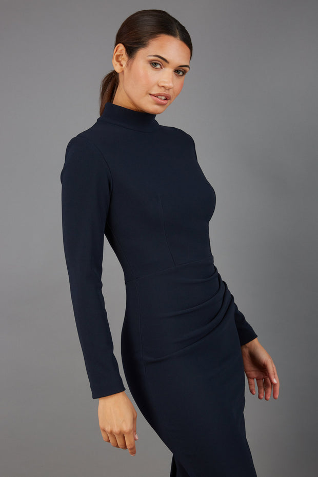 brunette model wearing diva catwalk sasha pencil-skirt dress with long sleeves and high neck in colour dark blue front
