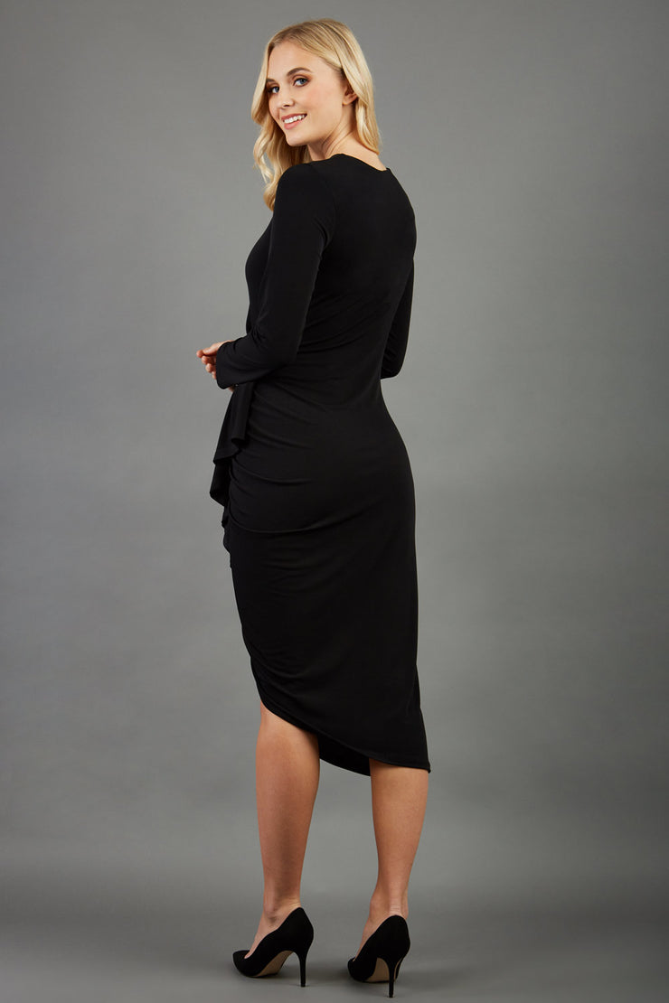 blonde model wearing diva catwalk black flamenco midaxi pencil dress with a frill down the side on the skirt with long sleeves in black front