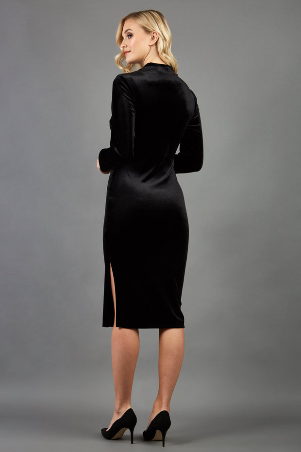 brunette model wearing diva catwalk clipper pencil skirt dress velvet sleeved style with a keyhole detail and high neck and split on a side of the skirt in colour black back