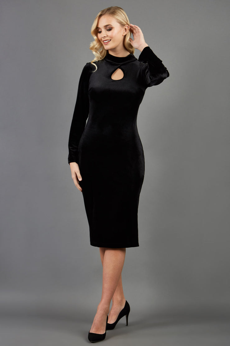 brunette model wearing diva catwalk clipper pencil skirt dress velvet sleeved style with a keyhole detail and high neck and split on a side of the skirt in colour black front