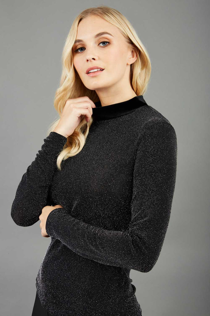 Blonde hair model is wearing a jersey sparkle velvet turtleneck blouse top  front image