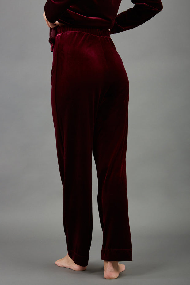 model wearing diva catwalk pelham stretch velvet straight leg trousers in velvet with ribbon in burgundy colour back