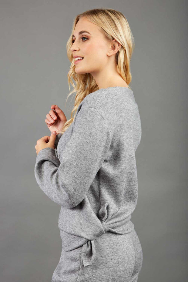 blonde model wearing diva catwalk muscari asymmetric sleeved top with rounded neck in flint grey front
