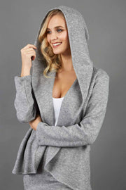 blonde model wearing diva catwalk cashmere hooded jacket with long sleeves and front waterfall closure in grey colour  front