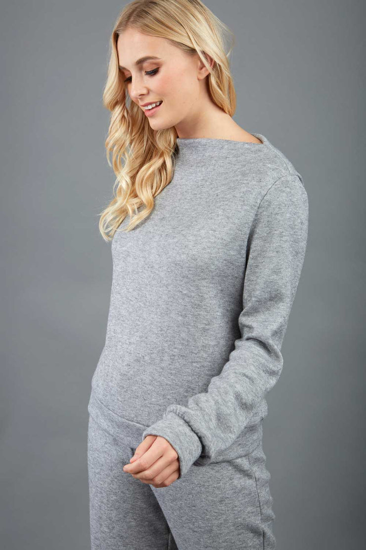 blonde model wearing diva catwalk hudson top with long sleeves and boat neckline in very soft cosy cashmere fabric in grey colour front with aria joggers matching the top front