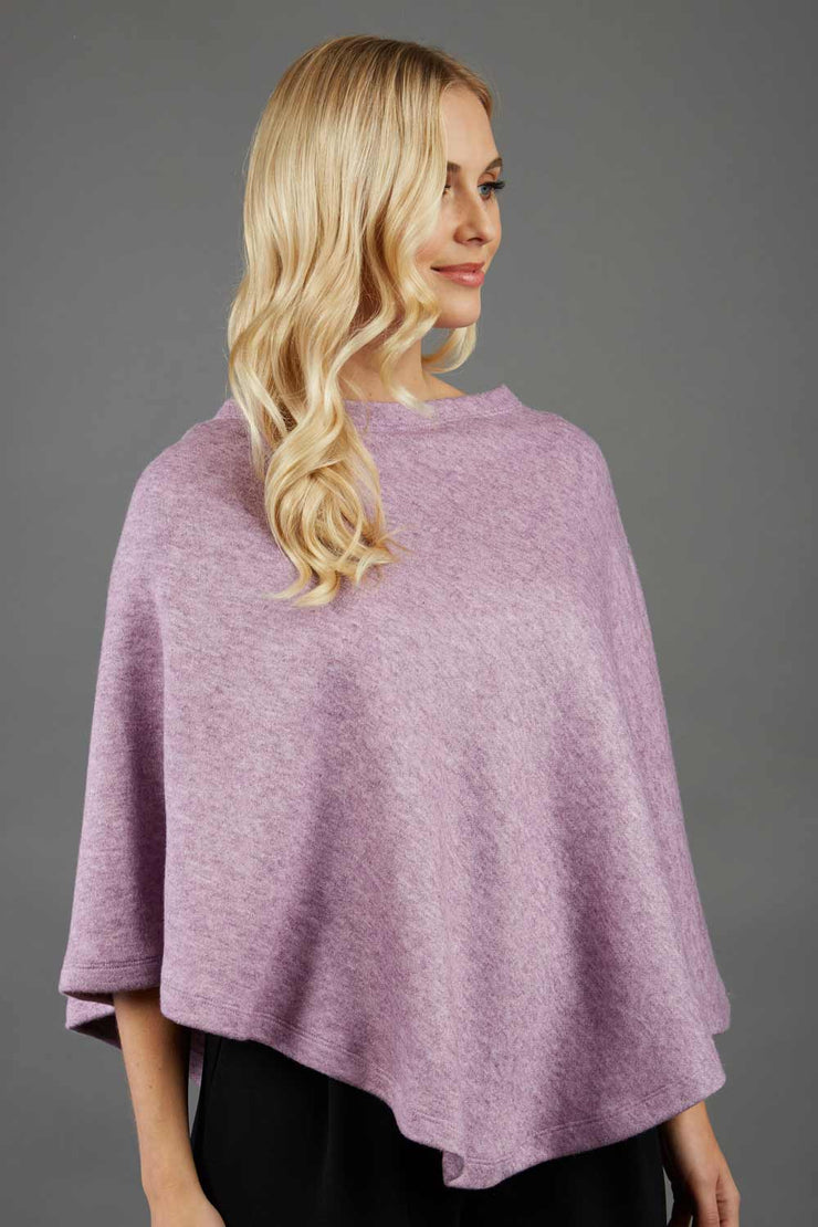 blonde model wearing diva catwalk rosalia poncho made in very cosy soft cashmere fabric in pale pink front