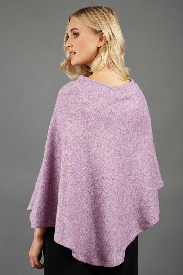 blonde model wearing diva catwalk rosalia poncho made in very cosy soft cashmere fabric in pink back