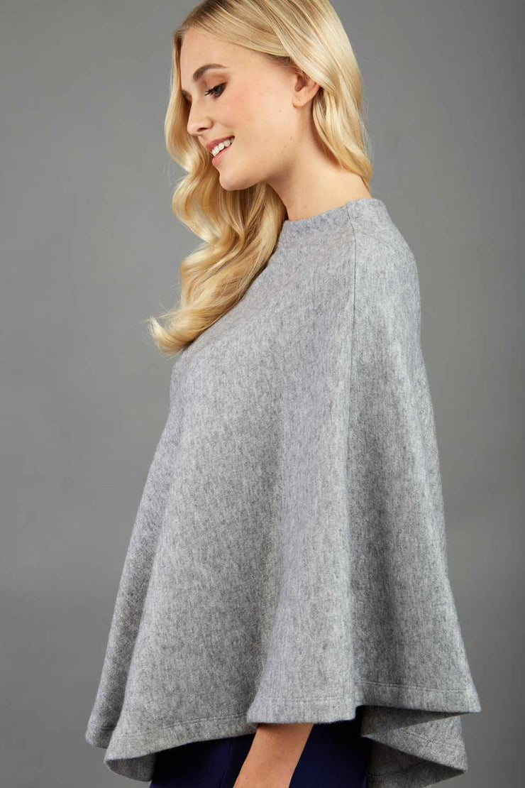 blonde model wearing diva catwalk rosalia poncho made in very cosy soft cashmere fabric in flint grey side