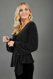 Blonde hair model is wearing a jersey sparkle v neck wrap blouse with bishop sleeve detail and bow on a side side image