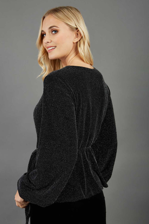 Blonde hair model is wearing a jersey sparkle v neck wrap blouse with bishop sleeve detail and bow on a side front back