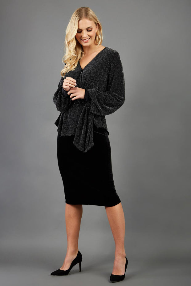 Blonde hair model is wearing a jersey sparkle v neck wrap blouse with bishop sleeve detail and bow on a side front image