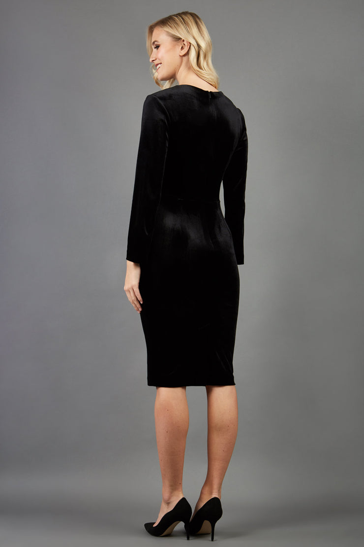 blonde model wearing diva catwalk celine black velvet pencil skirt dress with long sleeves and 3 bow details at the front in black back