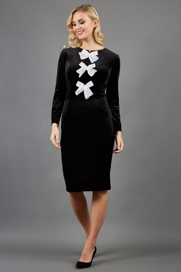 blonde model wearing diva catwalk celine black velvet pencil skirt dress with long sleeves and 3 bow details at the front in black front