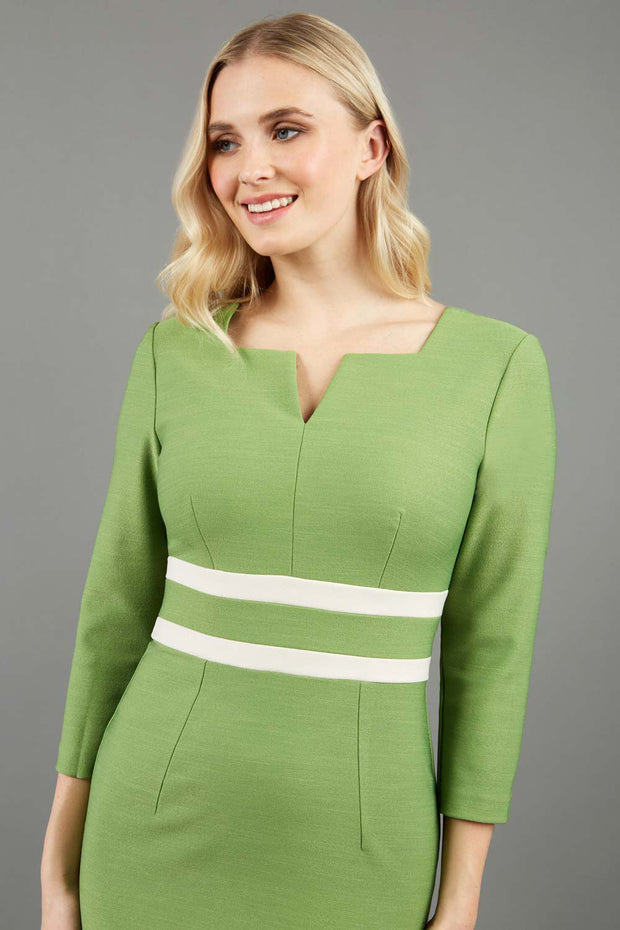 blonde model is wearing diva catwalk nandina pencil dress in citrus green with contrasting doubled waistband with sleeves front