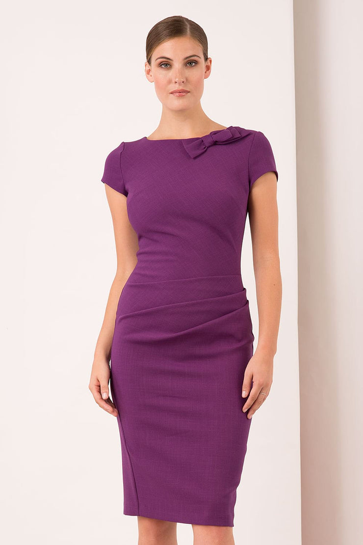 A model wearing a bow detail round neckline pencil knee length dress with pleating detail at the front in purple by Diva Catwalk