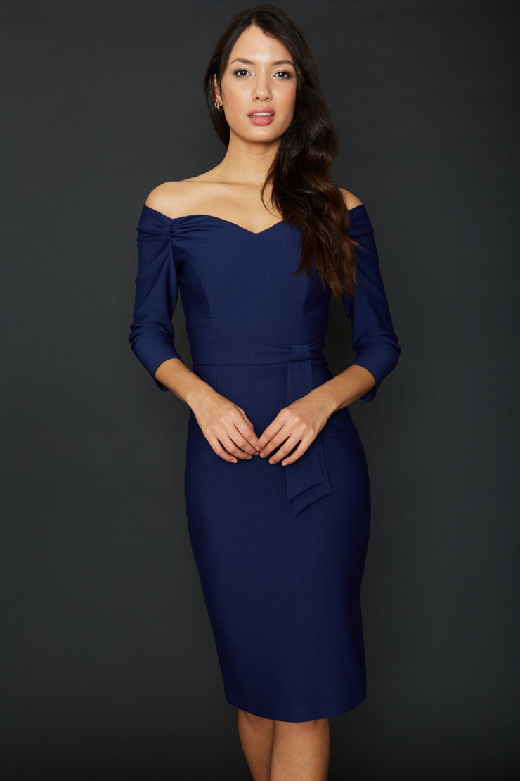 brunette model wearing diva alpa cocktail pencil dress in navy blue off shoulder style with sleeves and tie detail on waist knee length front