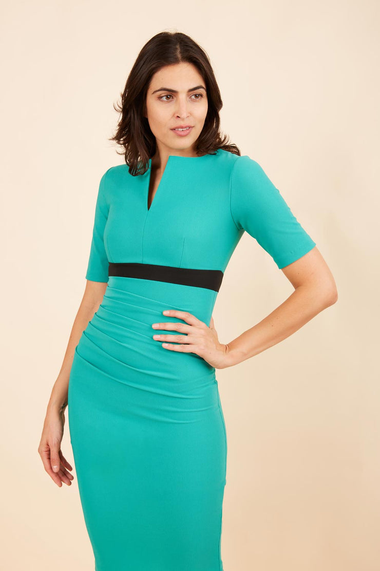 brunette model wearing diva catwalk nadia fitted dress with pencil pleated skirt with sleeves and rounded neckline with split in colour emerald green front