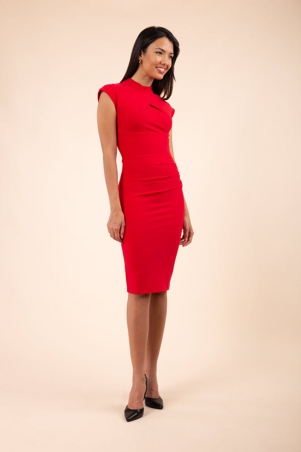 brunette model wearing diva catwalk beyonce pencil fitted dress with high neckline without sleeves with a wide band and pleating across the tummy area with a crossed detail neckline in scarlet red front