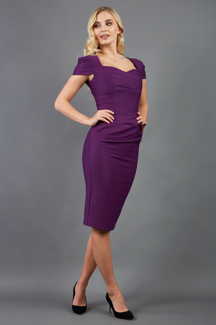 blonde model is wearing diva catwalk seed bonnie pencil skirt dress with cap sleeves and sweetheart neckline with pleating across the tummy in colour purple front