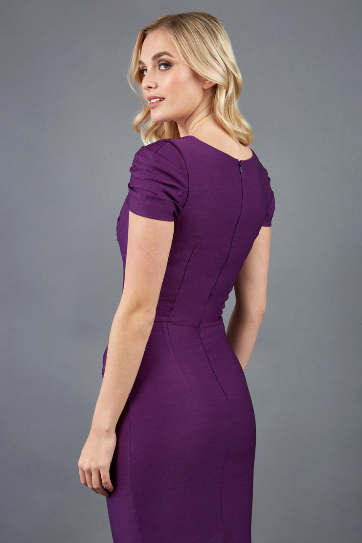 blonde model is wearing diva catwalk seed bonnie pencil skirt dress with cap sleeves and sweetheart neckline with pleating across the tummy in colour purple back