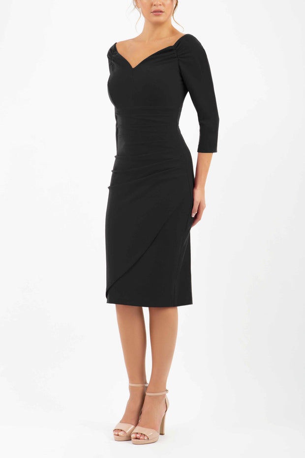 brunette model wearing diva catwalk evening pencil dress off shoulder with sleeves and pleated pencil skirt in colour black front