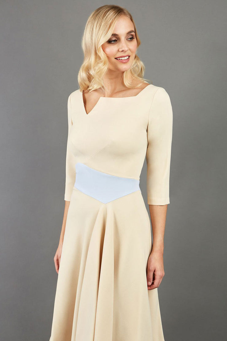 Blonde Model wearing Diva Catwalk Pinto Contrast swing a-line skirt Dress with asymmetric skirt and asymmetric neckline with three quarter sleeve in Sandshell Beige with Celestial pale blue front