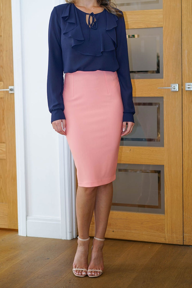 blonde model is wearing diva catwalk pencil skirt in peach paired with hambledon long sleeved top front