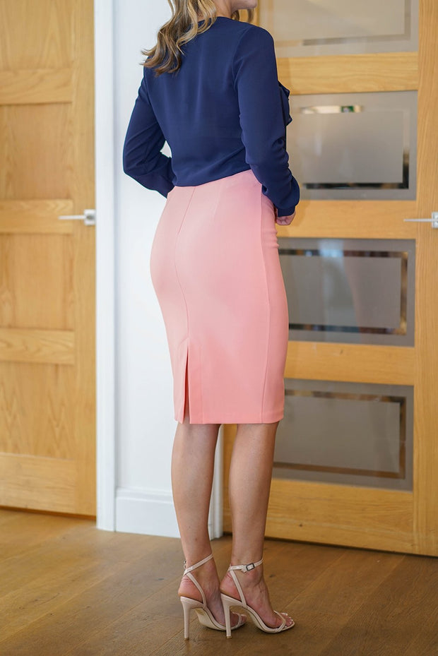 blonde model is wearing diva catwalk pencil skirt in peach paired with hambledon long sleeved top back