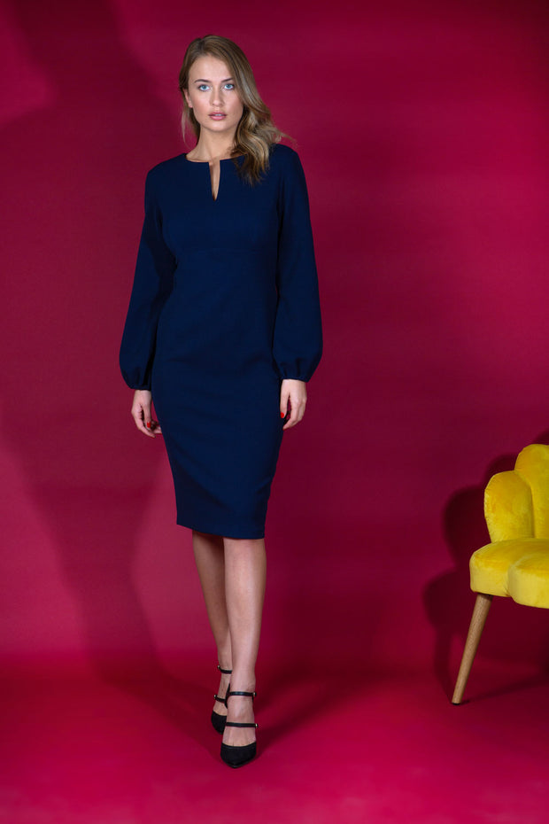 Blonde model wearing Diva Catwalk Praktica long puffed bishop sleeves knee length empire line pencil dress with round neckline with a slit cut in the middle in Navy Blue front