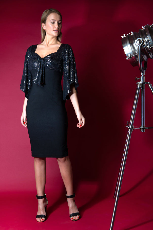 blonde model is wearing diva catwalk premiere pencil vintage sperkly dress with sleeves and empire waist in black front