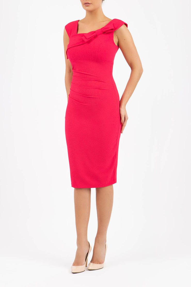 brunette model wearing diva catwalk rosita pencil skirt fitted dress with asymmetric neckline and bow detail at the top and it is a sleeveless design  with empire waistline in pink front