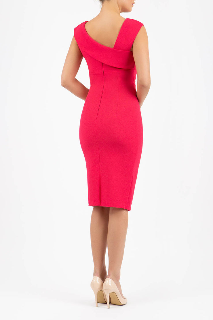 brunette model wearing diva catwalk rosita pencil skirt fitted dress with asymmetric neckline and bow detail at the top and it is a sleeveless design  with empire waistline in pink back