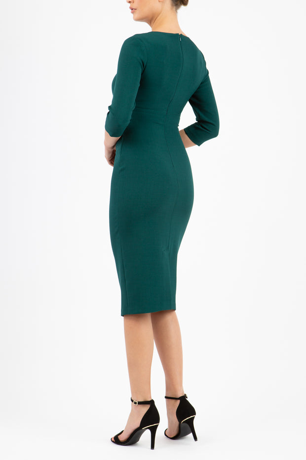 brunette model wearing diva catwalk ubrique pencil dress with a keyhole detail and sleeves in forest green back