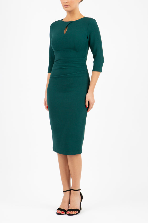 brunette model wearing diva catwalk ubrique pencil dress with a keyhole detail and sleeves in forest green front