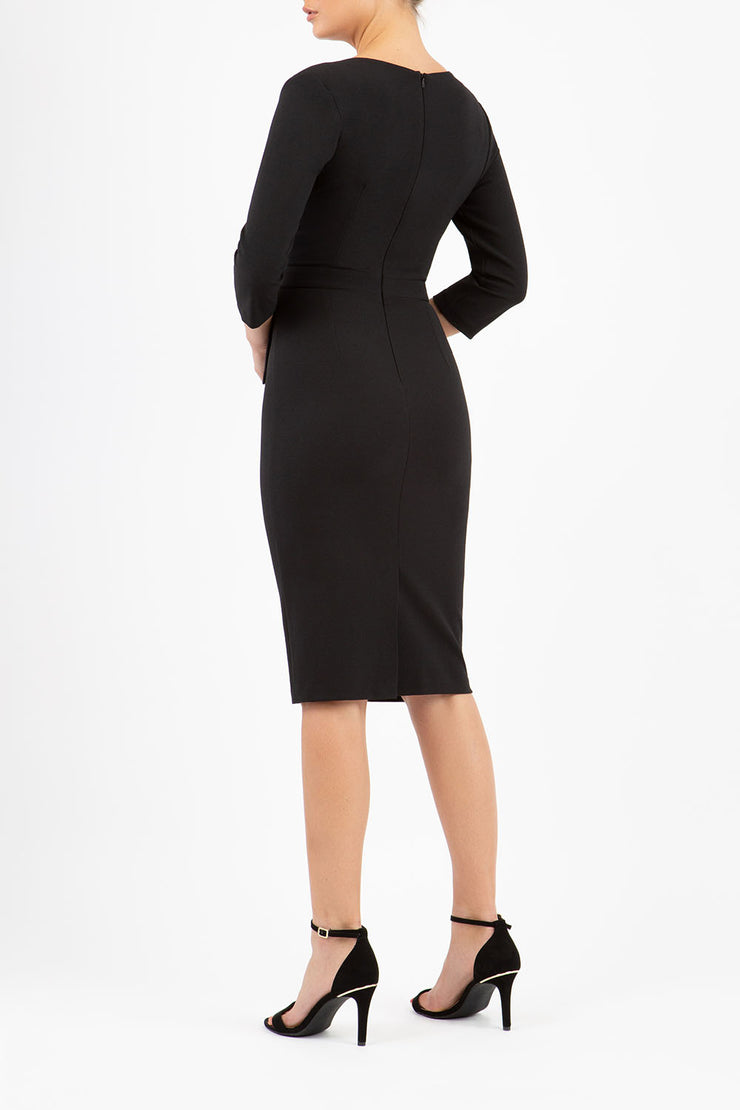 model wearing diva catwalk elan elegant black dress with 3 4 sleeves with a tie detail and asymmetrical closing back