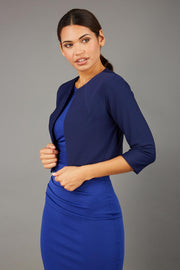 brunette model wearing diva catwalk navy sleeved bolero over a royal blue pencil dress front