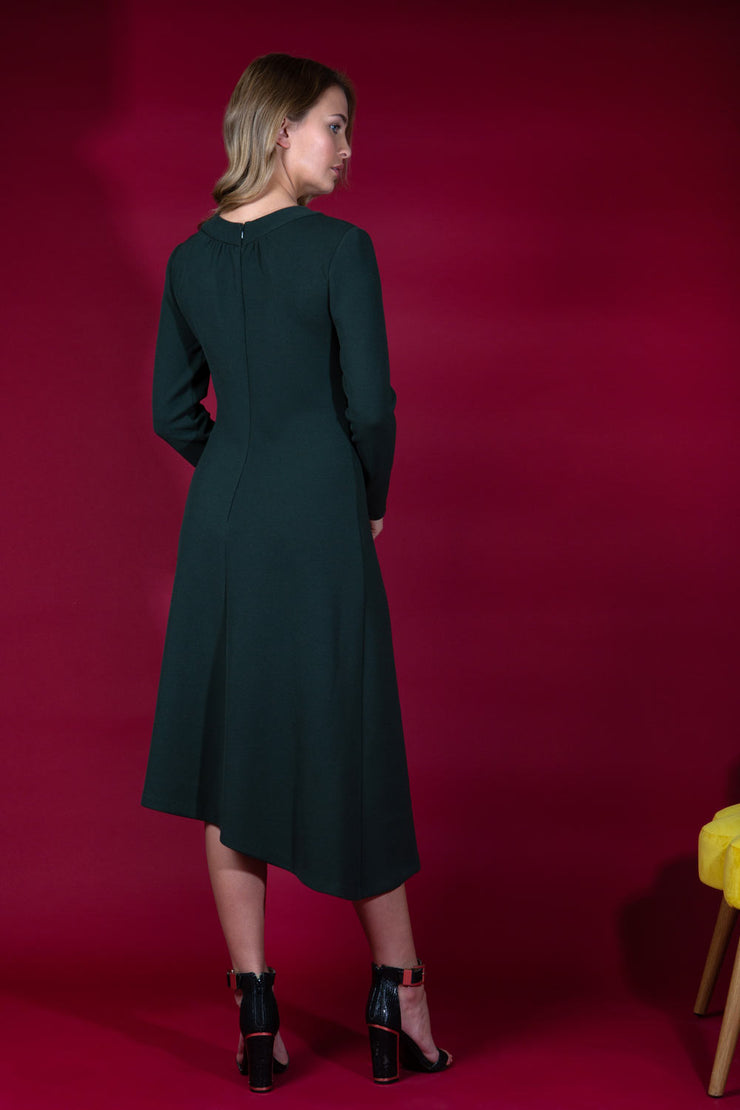blonde model is wearing diva catwalk dartington asymmetric skirt midaxi long sleeve dress with rounded pleated neckline a-line style in deep green back