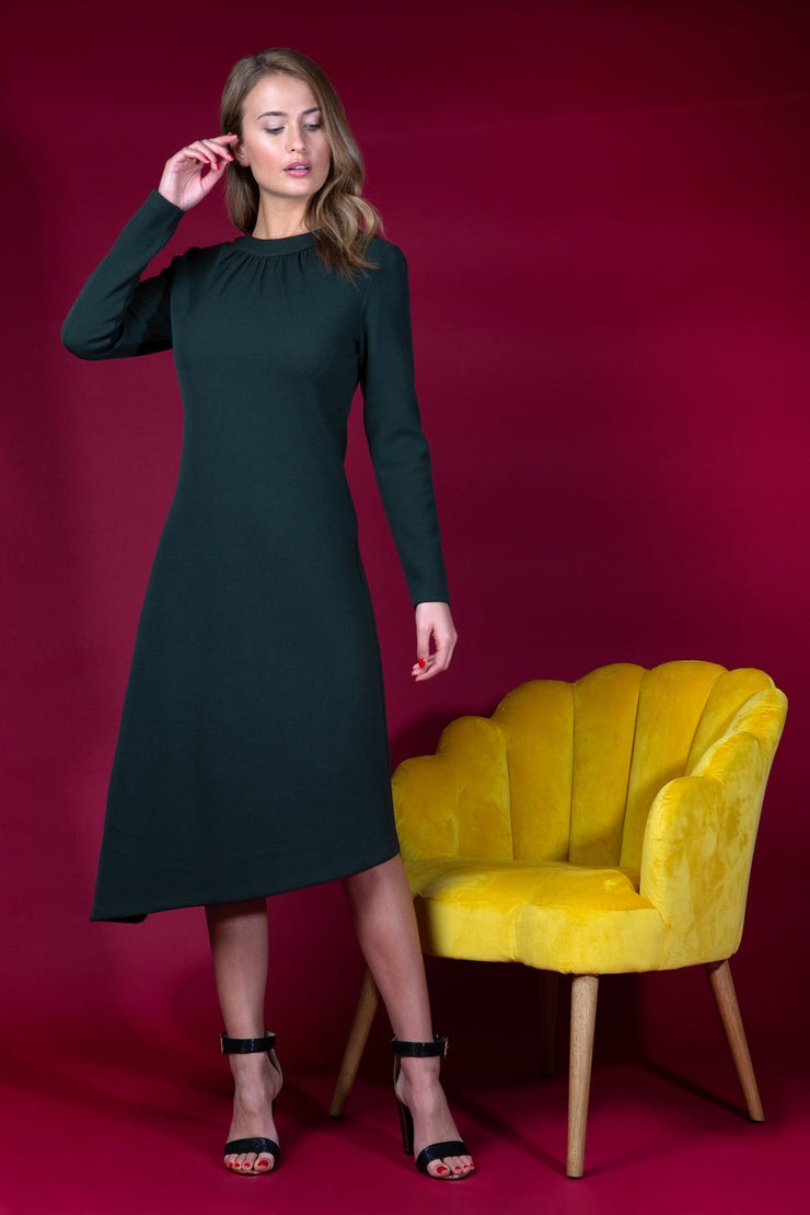 Model wearing the Diva Dartington Asymmetric Midi Dress with midi length and long sleeve in black front image