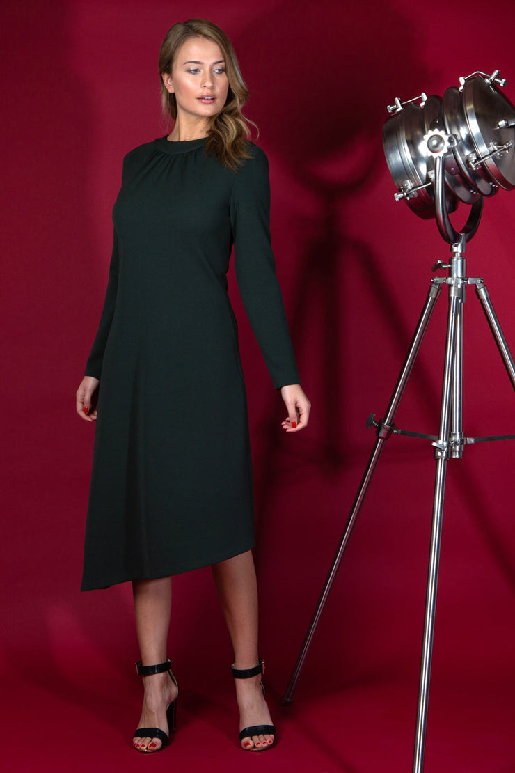 blonde model is wearing diva catwalk dartington asymmetric skirt midaxi long sleeve dress with rounded pleated neckline a-line style in deep green front